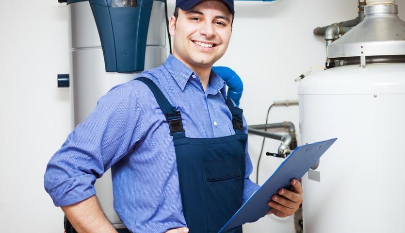 lächelnder Techniker im Heizraum - Hauskalkschutz